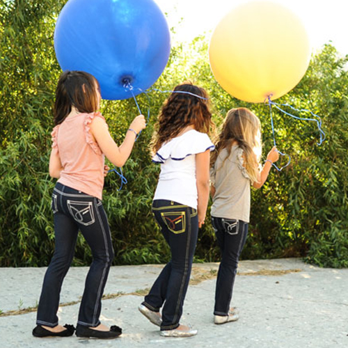 Stylish girls play with balloons while wearing clothing from Animal Crackers boutique